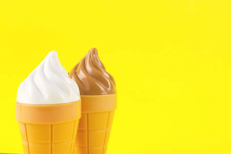 Ice cream toys made from plastic on yellow background 版權商用圖片