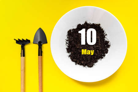 May 10th. Day 10 of month, Calendar date. White plate of soil with a small spatula and rake on yellow background. Spring month, day of the year concept