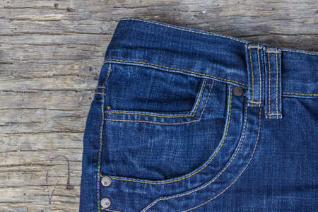 Top view of blue jeans on old wooden background