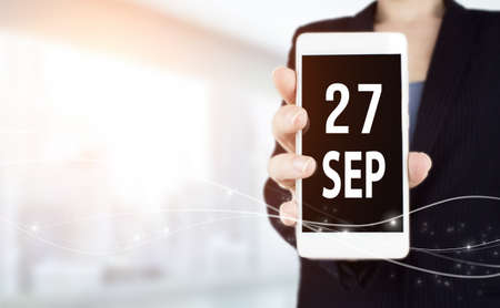 September 27th. Day 27 of month, Calendar date. White smartphone with Calendar date in businesswoman hand on blurred background. Autumn month, day of the year concept