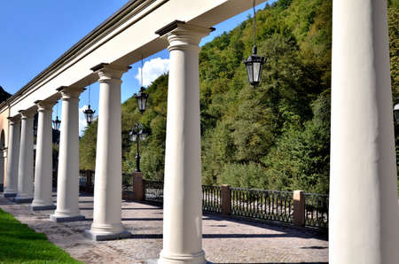 View of the embankment with colonnade of the river Mtsesta, Krasnaya Polyana, Sochi, Russia.