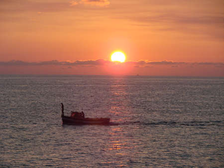 Boat with fishmans and sunset on Bleak See