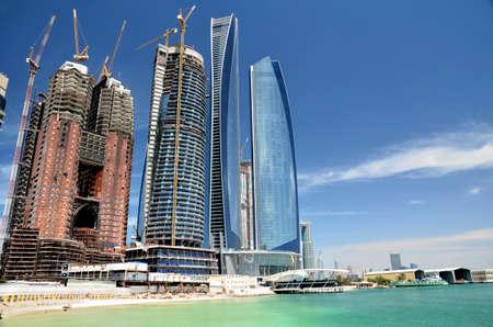 Window cleaners on a skyscraper in Abu Dhabi, United Arab Emirates Редакционное
