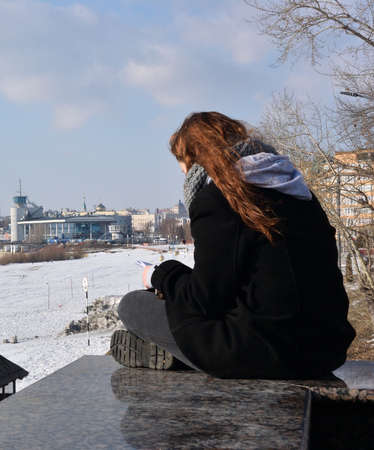 OMSK, RUSSIA -MARCH 2016: A girl with a smartphone on the background of the winter embankment of Irtysh
