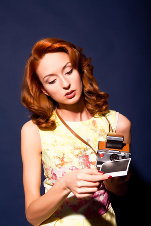 Girl with retro style camera and picture. photo