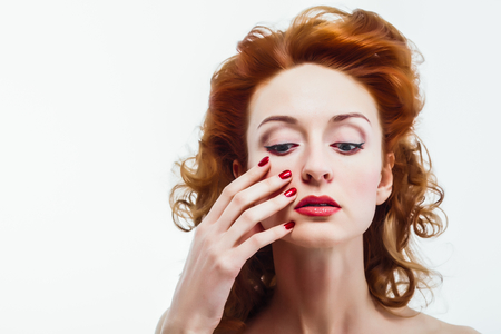 Beautiful woman touching face, clean skin, red hairs, red nails  White isolated background  photo