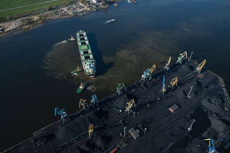 Coal port, top view. Mooring operations, sea vessel. Aerial.