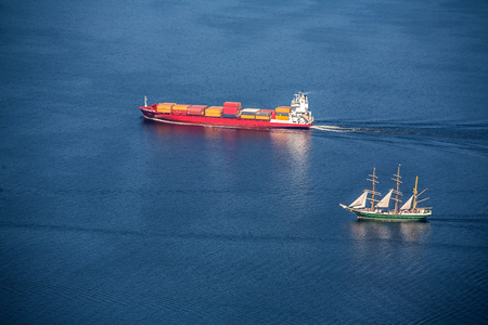 View from above. A sea vessel is a container ship  and Tall ship at full speed in the open sea.