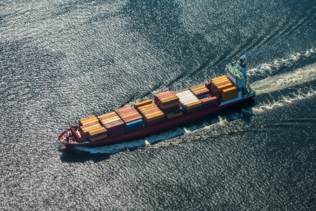 A sea vessel is a container ship at full speed in the open sea. View from above. 版權商用圖片