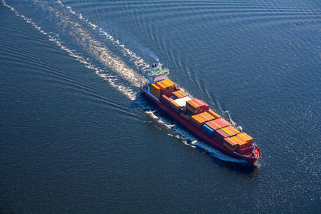 A sea vessel is a container ship at full speed in the open sea. View from above. Banco de Imagens