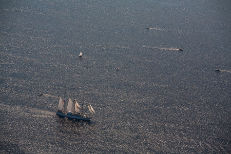 View from above. Several yachts and sailboats go to sea under sail.