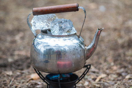 Travel kettle with ice on the primus fire. Gasoline fuel. Stock Photo - 105059600