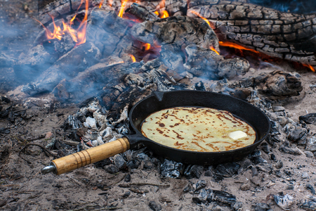 Cooking pancakes on the fire in the forest. Kitchen in forest.