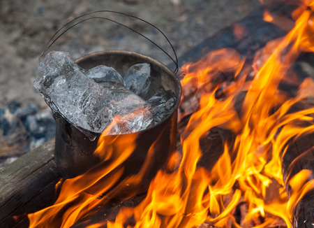 Cauldron with ice on fire in forest. Cooking in the nature.