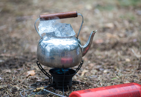 Travel kettle with ice on the primus fire. Gasoline fuel. Stock Photo