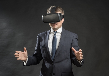 360. Virtual game. Man in black suit uses a virtual reality glasses.  VR Stock Photo