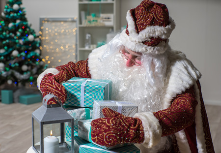 Santa Claus and his gifts. He thinks who to give gifts. Cristmas tree and latern. Banco de Imagens - 118376818