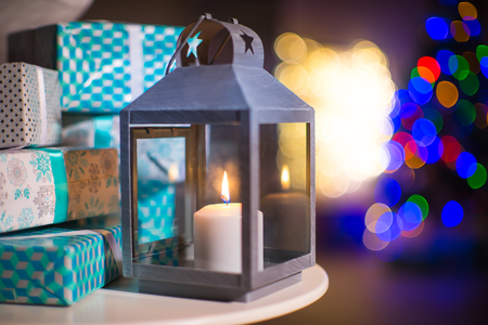 Beautiful vintage candle lantern on the background of New Year gifts and early-colored light bulbs.