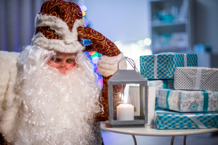 Santa Claus and his gifts. He thinks who to give gifts. Cristmas tree and latern. Banco de Imagens - 118377670