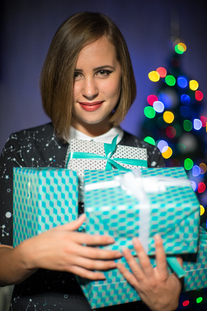 A girl with Christmas gifts and christmas tree on the background.