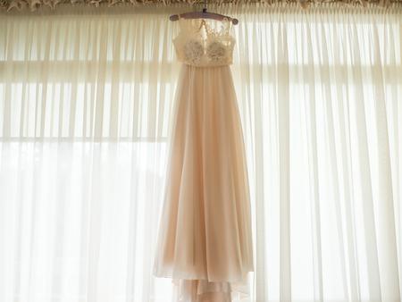 Light wedding dress on the background of the window