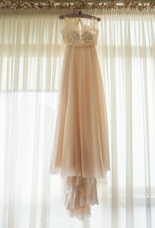 Chiffon dress hanging on the hanger on the background of the window. Banco de Imagens
