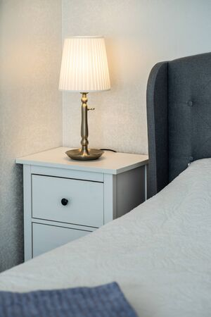 Small bedside near the bed with burning lamp. White walls.