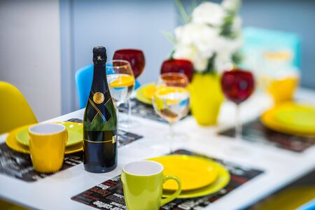 Focused bottle of champagne, Yellow dishes and cups. Wine glasses. Banco de Imagens