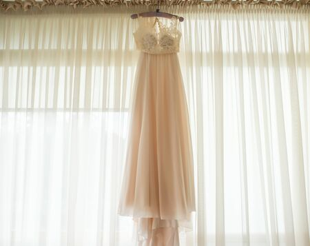 Chiffon dress for the bride hanging on the hanger on the background of the window. Banco de Imagens