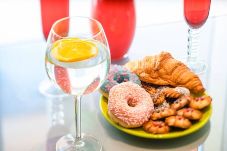 Lemon water in wine glass with donuts and cookie. Banco de Imagens