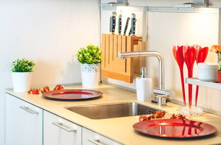 Modern kitchen. Knives in the wooden stand. Red plates. Banco de Imagens