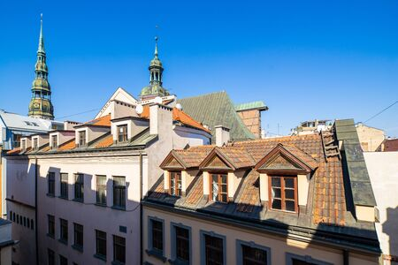 Sunny day. Blue sky. Old town of Riga. Tile roofs. Stock Photo