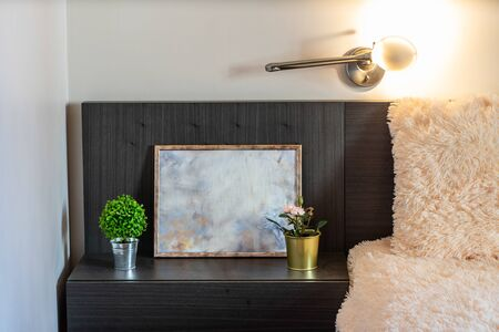 Picture near the bed in apartment. Decorative flowers. Banco de Imagens - 128815976