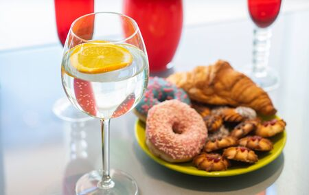Lemon water in wine glass with bakery on background.