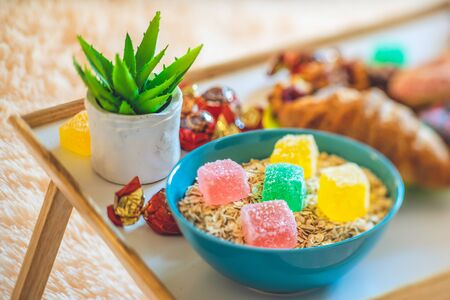 The bowl of cereal with colorful marmalade. Sweets, flower and pastry.
