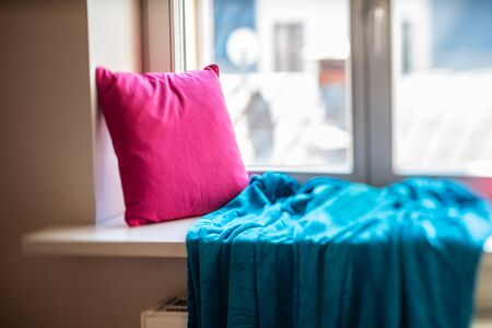 Cozy windowsill with pink pillow and blue blanket.