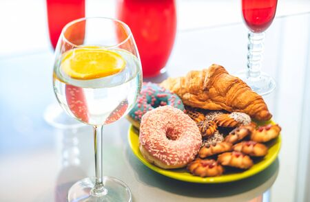 Lemon water in wine glass with pastry on background.
