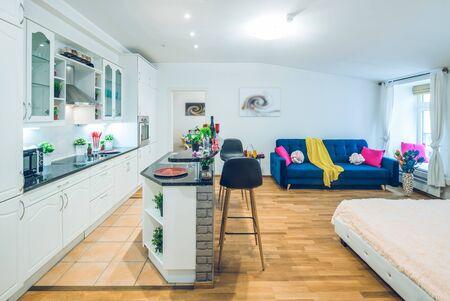 White kitchen set. Cozy blue sofa. Blurred pictures. Decorative elements. Banco de Imagens - 128816332