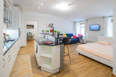 White kitchen set. Cozy blue sofa. Blurred pictures. Decorative elements. Banco de Imagens - 128816375