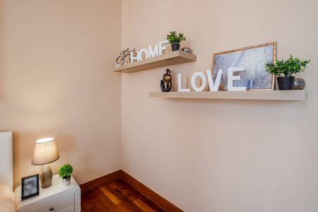 Wooden signs Home and Love on the shelves. Decorative flowers. Banco de Imagens