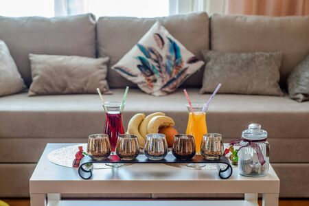Small table. Cocktails and fruits. Cozy sofa with pillows.
