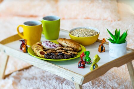 Couple of mugs with coffee. Wooden tray. Delicious cookie. Bowl with flakes. 写真素材