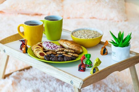 Couple of mugs with coffee. Wooden tray. Delicious cookie. Bowl with flakes. Banco de Imagens