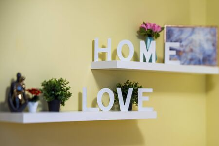 Decorative sign. Blurred picture. Flowers and statuettes. Archivio Fotografico