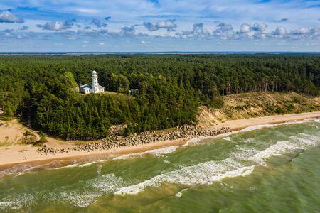 White Uzhava lighthouse on the shore of Baltic Sea. Sunny day. Banco de Imagens - 129014981