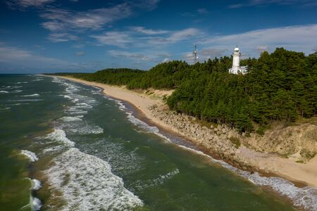 White Uzhava lighthouse on the shore of Baltic Sea. Sunny day. Banco de Imagens - 129014982