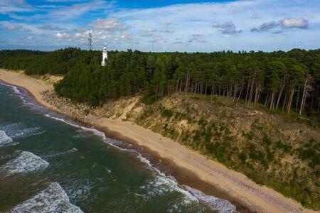 White Uzhava lighthouse on the shore of Baltic Sea. Sunny day. Banco de Imagens - 129014983