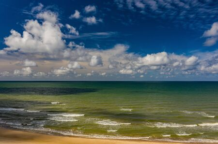 Beautiful view of the sea. Cloudy day. Blue sky. Sand beach. Banco de Imagens - 129014996