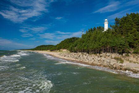 White Uzhava lighthouse on the shore of Baltic Sea. Sunny day. Banco de Imagens - 129015019