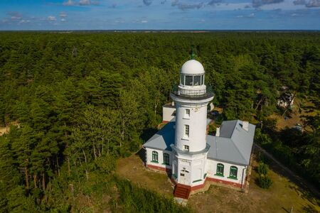 White Uzhava lighthouse. Sunny summer day. Cloudy sky. Banco de Imagens - 129015015